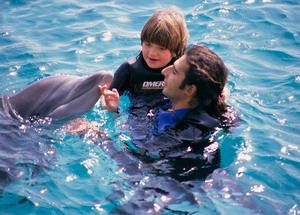 Ребенок играет с дельфином